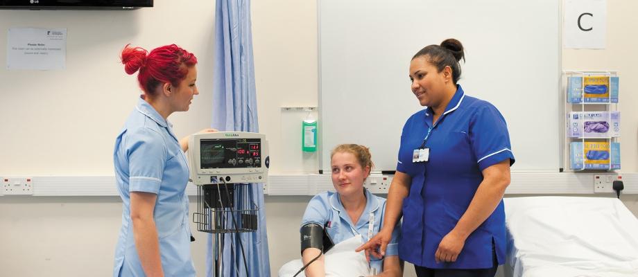 Female undergraduate student having her blood pressure checked, QMC