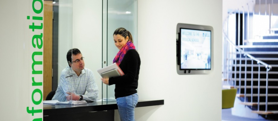 Female postgraduate student at a information desk, Medical School foyer