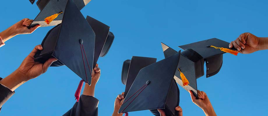 Hands throwing mortarboards into the sky