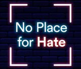 'No Place for Hate' neon text on a blue brick background