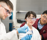 Three people in a lab handle a sample
